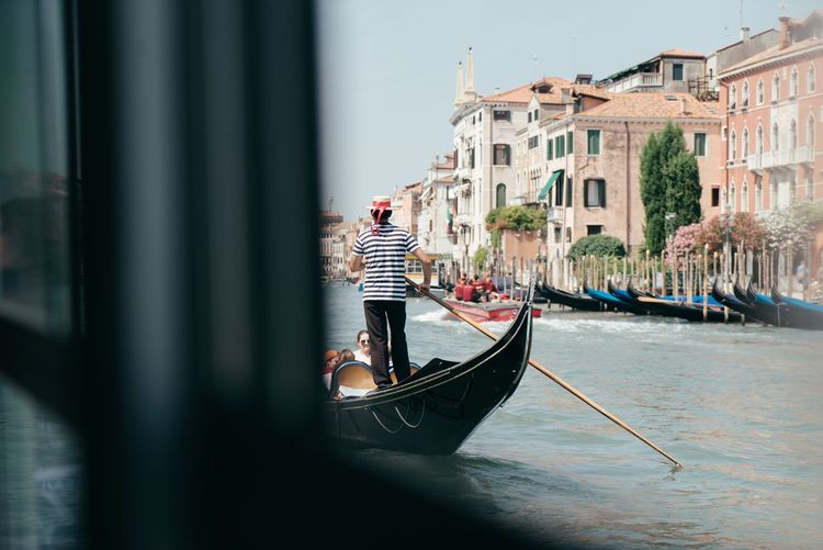 Rear view of man rowing gondola in grand canal