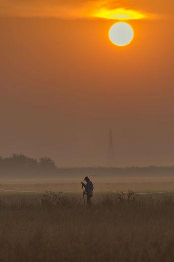 Man standing on field against orange sky