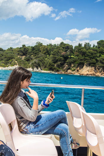 Side view of young woman using mobile phone while traveling in boat