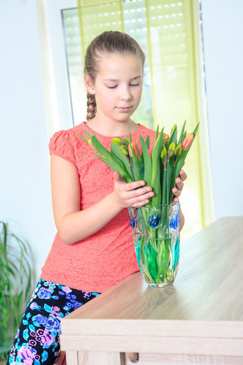 Teenage girl holding flowers in vase on wooden table at home