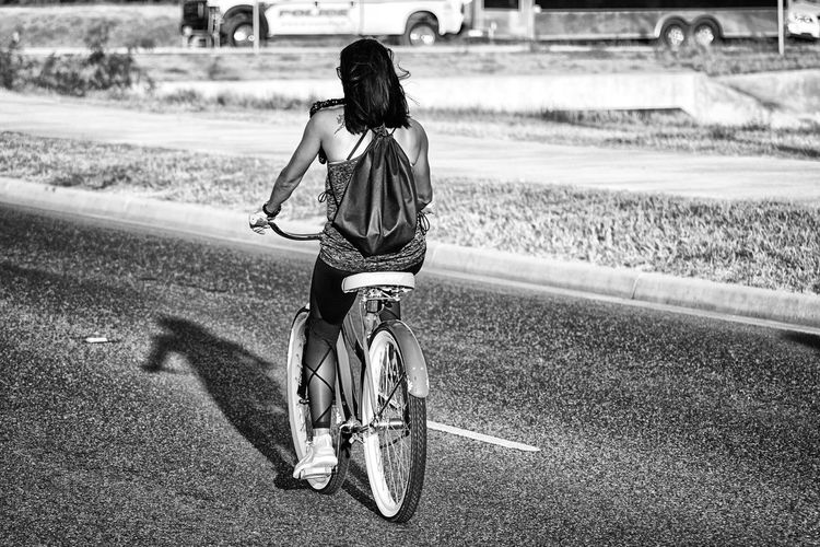 Sadow Bicycle Black And White Casual Clothing Childhood Day Full Length Hairstyle Land Vehicle Leisure Activity Lifestyles Mode Of Transportation Motion One Person Real People Rear View Ride Riding Road Transportation Women Nature