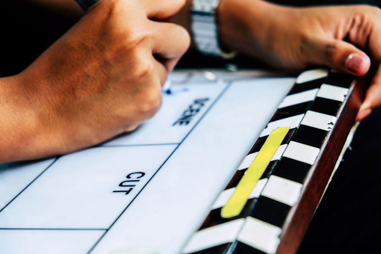 Close-up of hand writing in clapboard