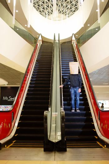 a man with a paper bag on his head standing on an escalator in the Mall Bag On Head Hipster Architecture Staircase Built Structure Steps And Staircases Indoors  Railing Low Angle View Escalator Modern Building