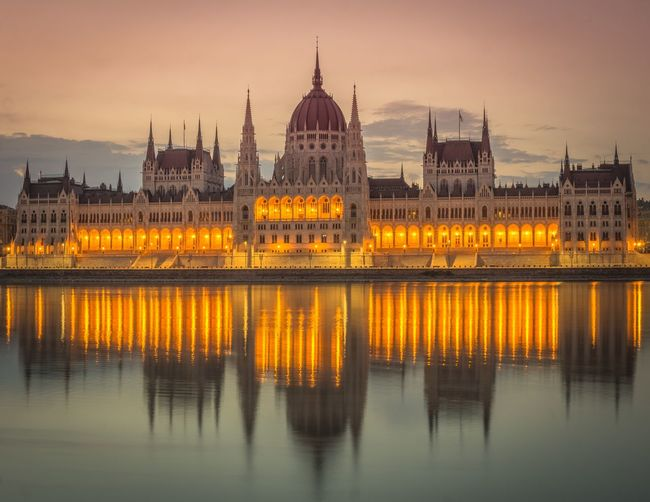 Illuminated hungarian parliament building by river at dusk