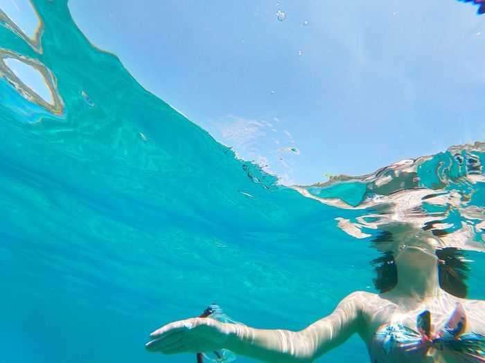 Low angle view of woman swimming underwater
