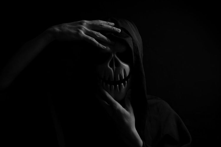 Close-up of person wearing mask standing against black background