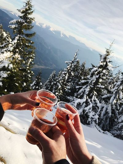 Close-Up Of Hands Toasting Drink Against Mountains