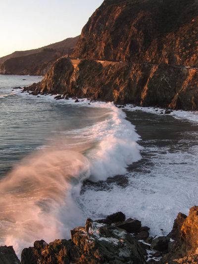 Waves rushing towards cliff