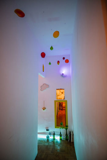Multi colored balloons against wall at home