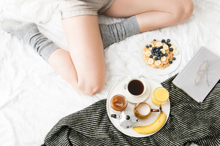 Low section of woman by breakfast on bed at home