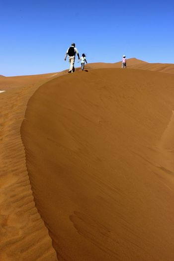 Man On Sand Dune In Desert Against Clear Sky