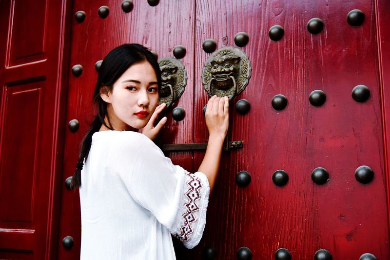 Rear view of woman holding door knocker