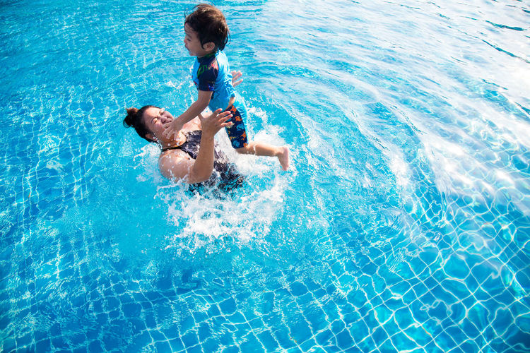 Cheerful mother and son in swimming pool