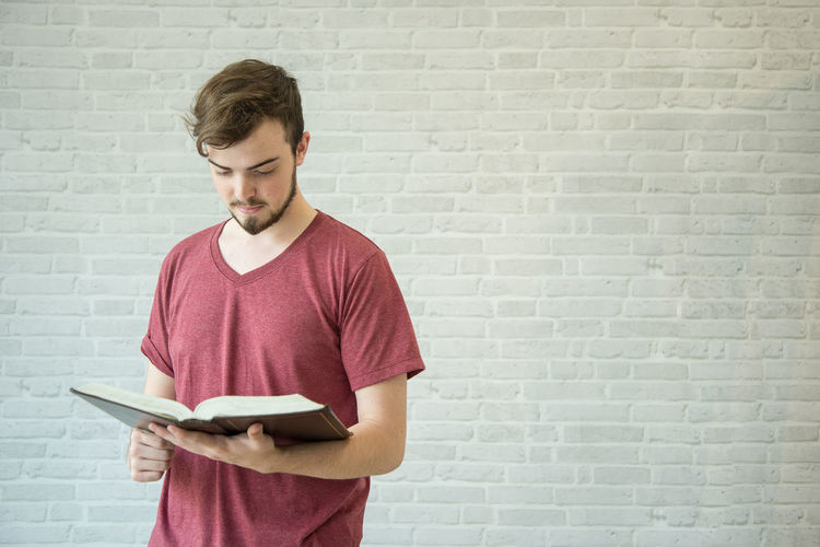 Young man reading bible while standing against brick wall