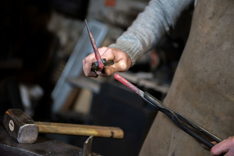 Midsection of blacksmith in workshop
