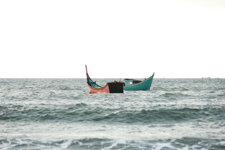 A pair of traditional fishing boats, going out to sea, looking for fish