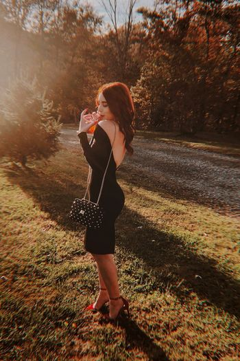 Side view of young woman drinking juice while standing on field in park during sunset