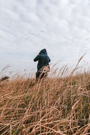 Rear View Of Man Standing On Grassy Field Against Cloudy Sky