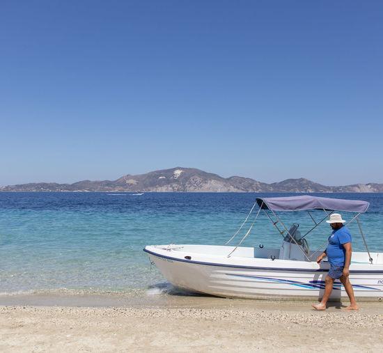 Man on beach against clear blue sky