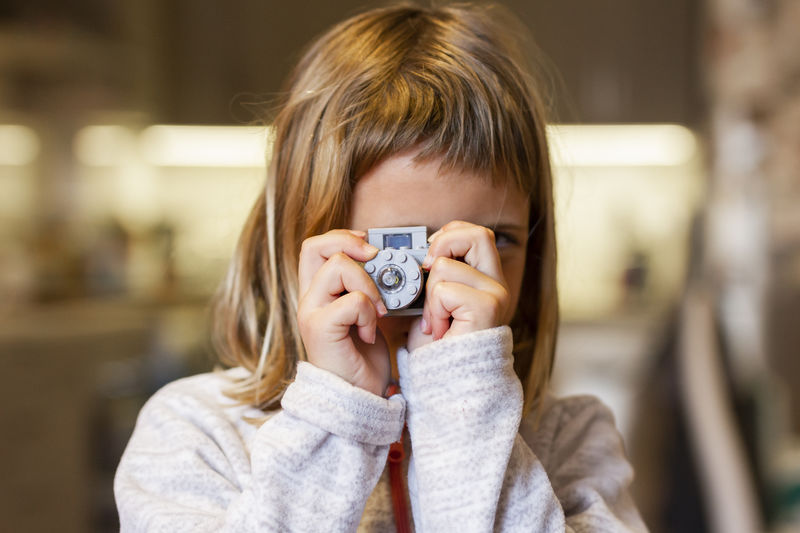 Close-up portrait of a girl holding camera