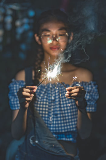 Young woman holding sparklers at night