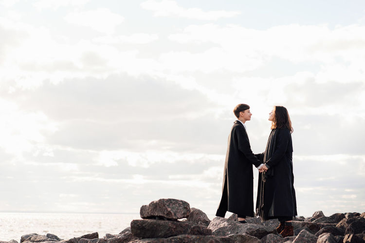 Couple standing on rock against sky