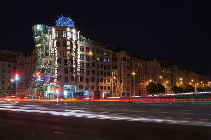 Light trails on city street against buildings at night