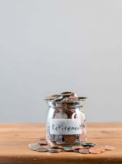 Savings in small coins in a glass bottle on wooden shelf for retirement 401K Poor  Cash Full Future Investment Investments Money No Money Not Enough Overflowing Pension Pension Plan Retirement Retirement Plan Savings Wealth Wealthy