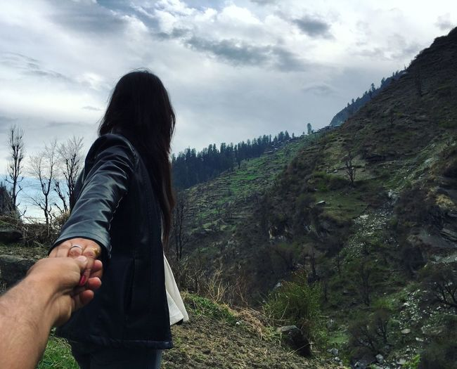 Cropped image of man holding girlfriend hand while walking towards mountains