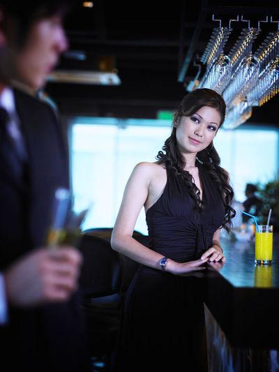 Young Woman Looking At Businessman Drinking At Bar