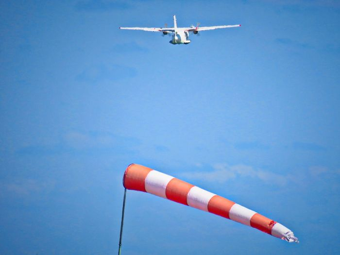 Low angle view of airplane and windsock flying against sky