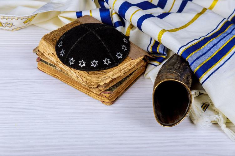 Hebrew handwritten Torah, on a synagogue alter, with Kippah and Talith shofar ram's horn Passover Rosh Hashanah Talith Yom Kippur Kippah Pessah Prayer Prayer Shawl Religious Celebration Shavuot Shofar