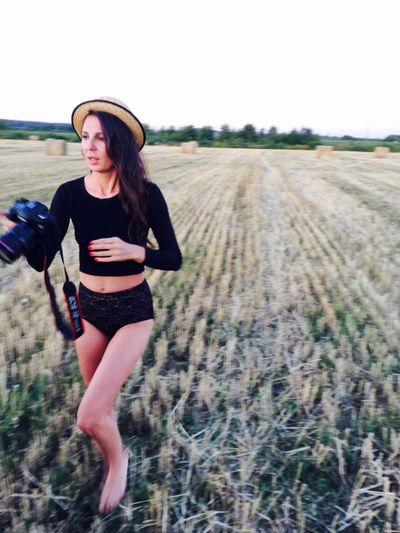 Full length of seductive woman holding camera while walking on agricultural field