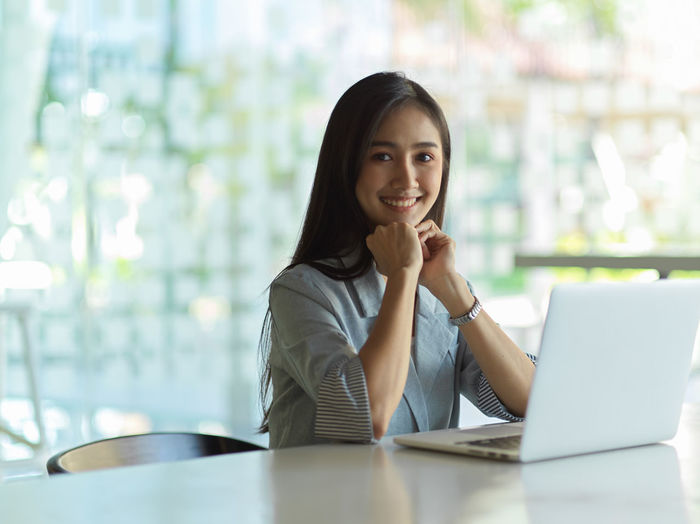 Portrait of young businesswoman sitting at office