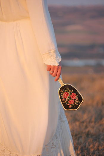 Midsection of woman holding hand mirror while standing on field during sunset