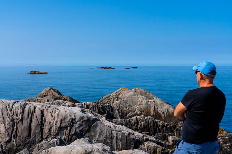 View from Utslåttøy Beauty In Nature Blue Horizon Over Water One Person Outdoors Real People Rear View Rock - Object Sea Sky Water