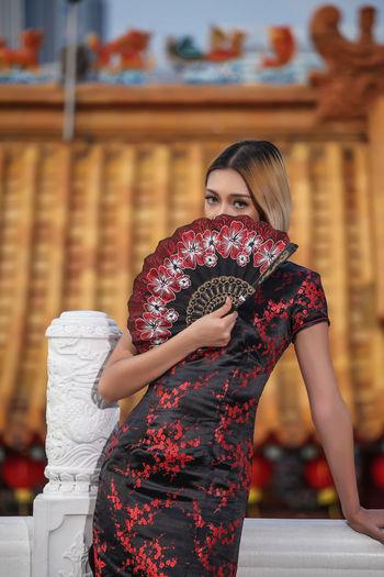 Portrait of woman holding folding fan