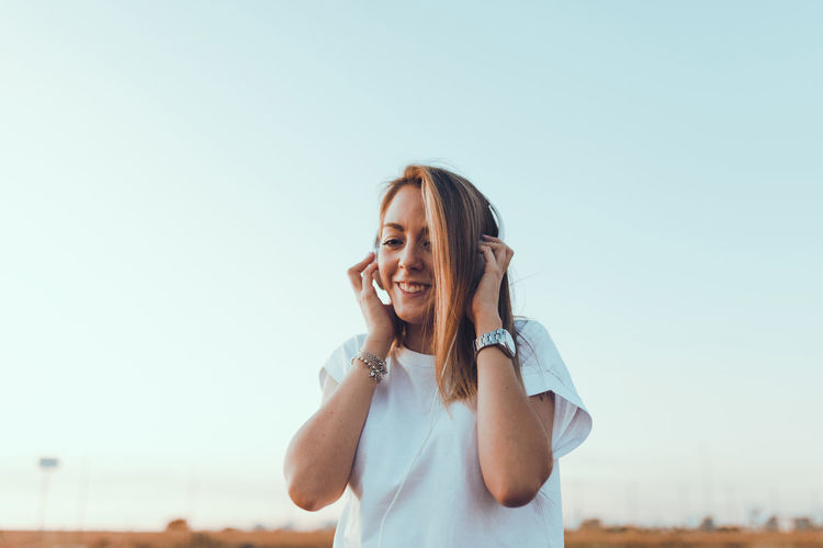 Portrait of smiling young woman against clear sky