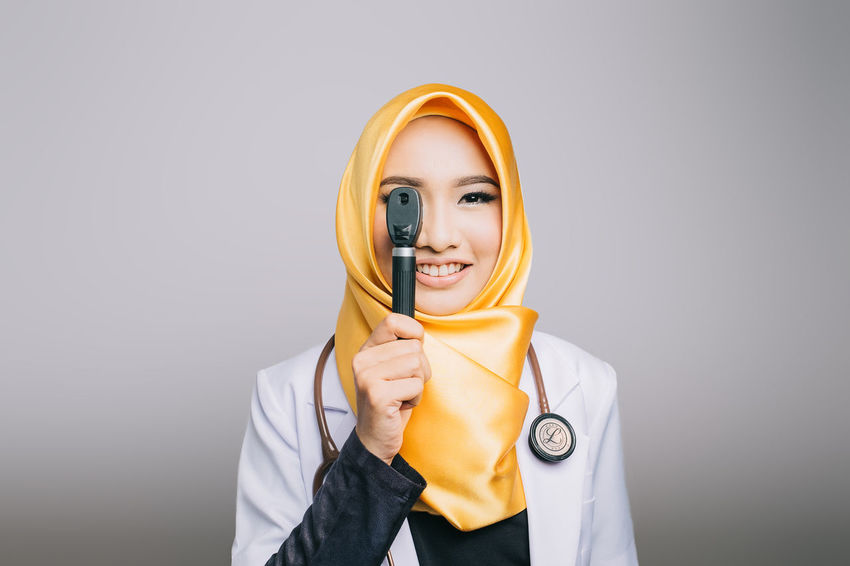 A Portrait of dr. Desy Women Around The World Doctor  Facial Expression Front View Hijab Holding Looking At Camera Portrait Studio Shot Vibrant Color White Background Woman Portrait Woman Who Inspire You Yellow Yellow Color Young Adult The Portraitist - 2017 EyeEm Awards Paint The Town Yellow