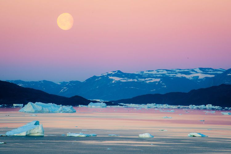 sunset and moonrise in beautiful island Uumannaq in the story i was so lucky to get invited by the local people to their home, offered me applepie and at the golden light the whole family took me to the beautiful Uummnaq mountain which means HEART in Greenlandic langauge. Greenland Arctic Beauty In Nature Cold Temperature Environment Idyllic Landscape Mountain Mountain Range Nature No People Non-urban Scene Orange Color Pink Color Purple Scenics - Nature Sky Snow Snowcapped Mountain Sunset Tranquil Scene Tranquility Uumannaq