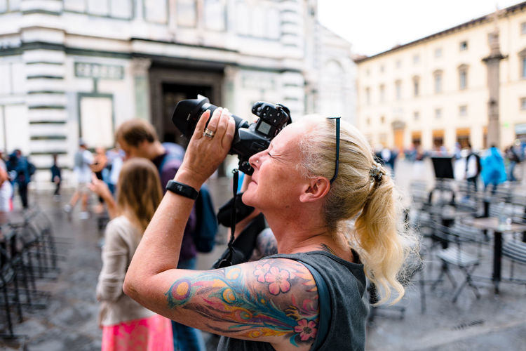 Side view of mature woman photographing while standing in city