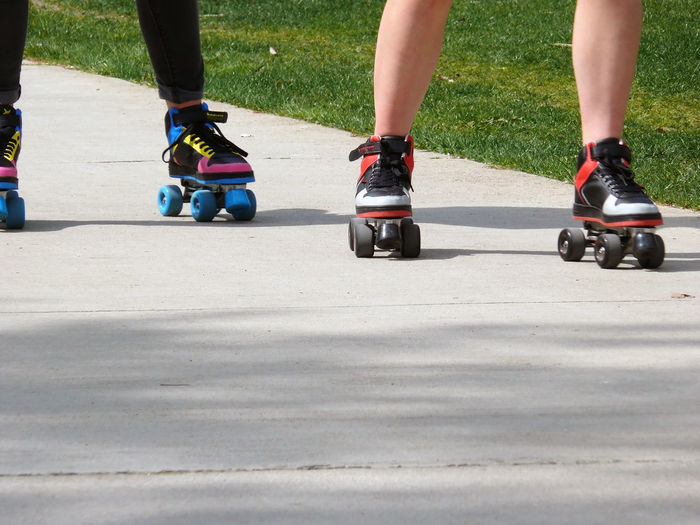 Low Section Of People Roller Skating On Street