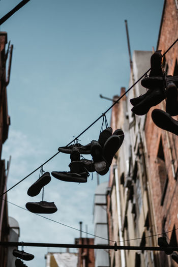 Low angle view of shoes hanging on cable