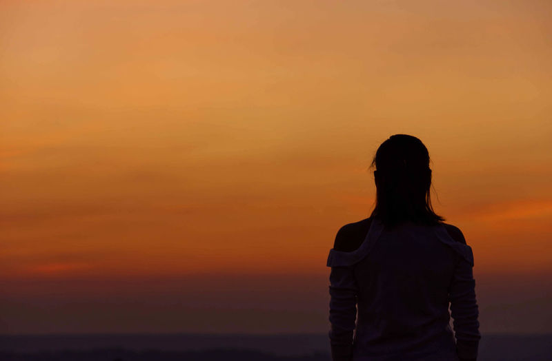 Rear view of woman standing against orange sky