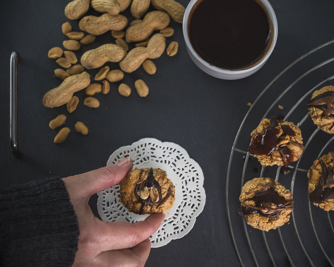 Cookies with peanuts - a woman hand reaches for it Cake Rack Chocolate Chocolate Covered Cookies Homemade Paper Lace Peanut Biscuit Peanuts Shortcrust Pastry Vintage Style American Food Baking Black Candy Chopped Nuts Crunchy Human Body Part Manufacturing Peanut Butter Recipe Slate Still Life Studio Photography Sweet Womans Hand Food Stories