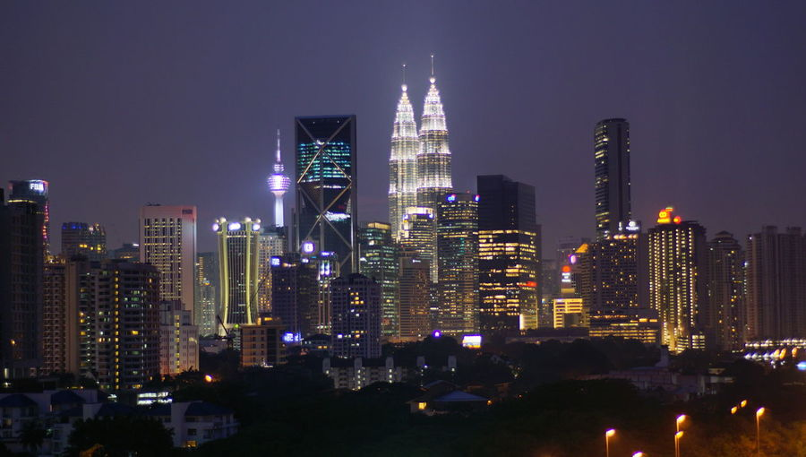 Malaysia city skyline illuminated at night. Architecture Building Building Exterior Built Structure City City Life Cityscape Financial District  Illuminated Landscape Modern Night Nightlife No People Office Office Building Exterior Outdoors Sky Skyscraper Spire  Tall - High Tower Urban Skyline