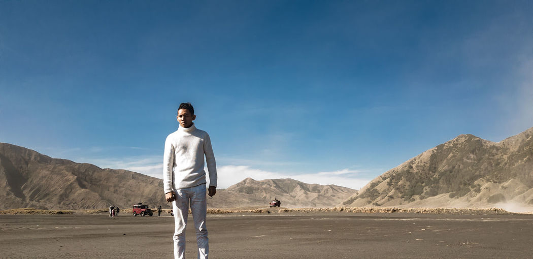 Portrait of man standing at desert against mountain