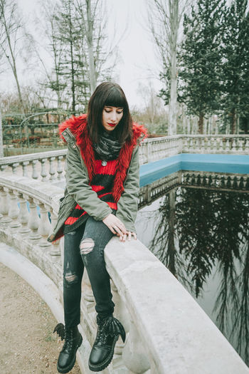 Thoughtful woman in warm clothing sitting at railing against lake