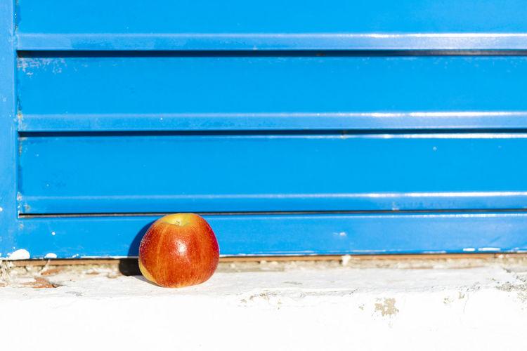 Red apple on a blue window