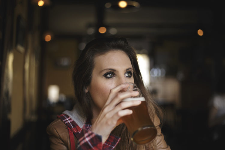 Young Woman Looking Away While Drinking Beer In Bar